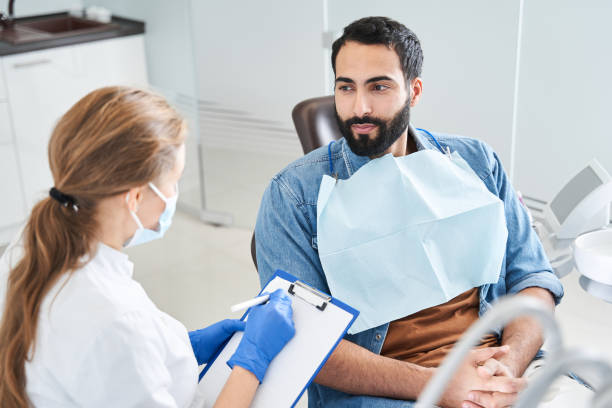 Back view of the blonde female dentist in dental office talking with multiracial male patient and preparing for treatment. Handsome bearded man in dentist chair looking at his doctor with smile, close up